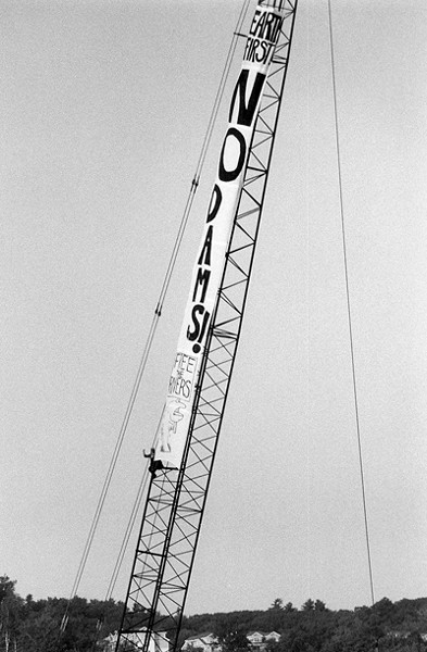 A climber on crane protests the construction of a hydroelectric dam on the Winooski River in solidarity with Vermont's Abenaki tribe. (1992) - PHOTO COURTESY OF ORIN LANGELLE