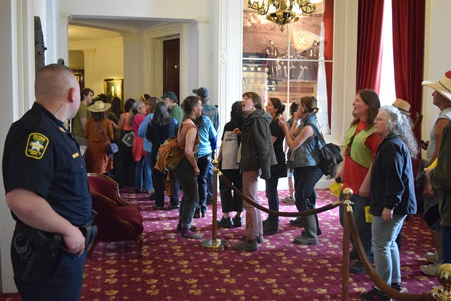 Protesters chant outside the House and Senate chambers Friday as police stand by. - TERRI HALLENBECK
