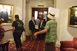 Protesters pass by the Senate chamber as Senate President Pro Tempore John Campbell and Sergeant-at-arms Janet Miller look on. - TERRI HALLENBECK