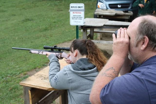 Amanda and Joe Corcoran sight a .22-caliber hunting rifle