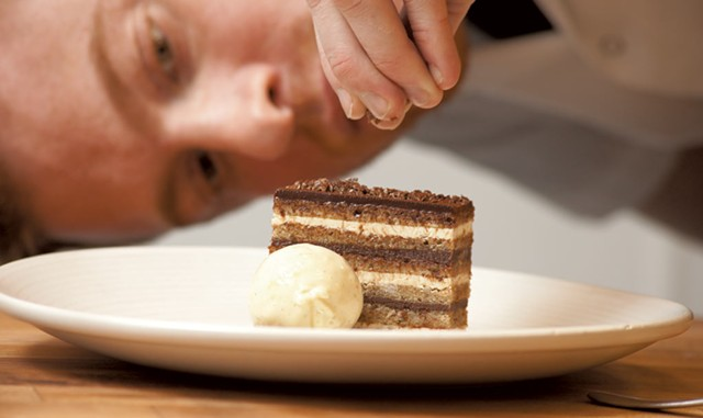 Andrew LeStourgeon completes an opera cake at Hen of the Wood