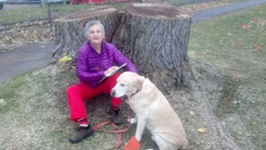 Ann Taylor and her dog by the stump of the tree she tried to save.