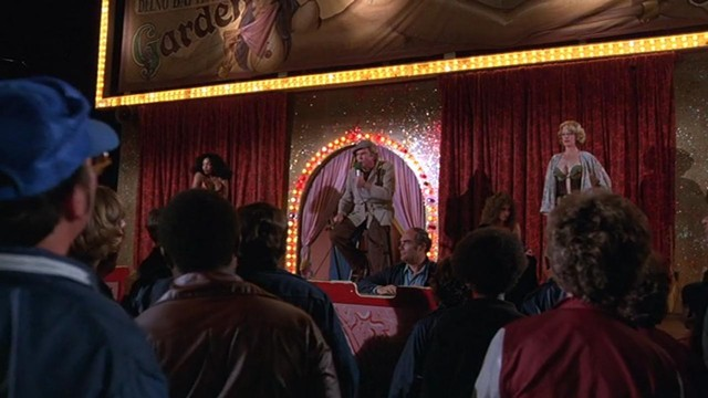 Bert Remsen, flanked by burlesque dancers, in Carny. - WARNER BROS. PICTURES