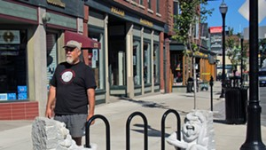 Calais sculptor Chris Miller on Main Street with the sculptural bike rack he created