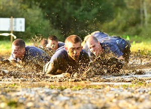 JEB WALLACE-BRODEUR - Competitors crawl through a mud pit during the 2012 Walter N. Levy Marine Corps Endurance Challenge at Norwich University
