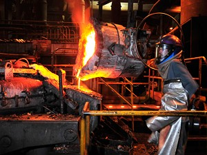 JEB WALLACE-BRODEUR - Eric Shepard pours molten metal from a ladle into a furnace at the Vermont Castings foundry in Randolph