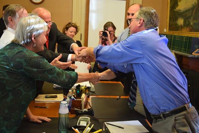 House and Senate education conferees shake hands after reaching an agreement on a school district consolidation bill Thursday evening. - TERRI HALLENBECK