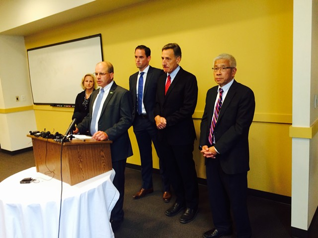 Lawrence Miller, senior advisor to Gov. Peter Shumlin, speaks at the press conference on the Vermont Health Connect website. Shumlin and Agency of Human Services Secretary Harry Chen are standing to the right of Miller. Representatives from Optum, the state's vendor managing the project, are also shown. - MARK DAVIS