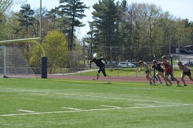 Muji Karim, far left, races Burlington High School track athletes. - ALICIA FREESE