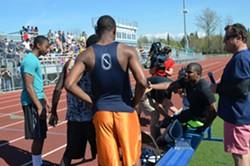 Muji Karim talks with Burlington High School athletes while putting on his running blades. - ALICIA FREESE