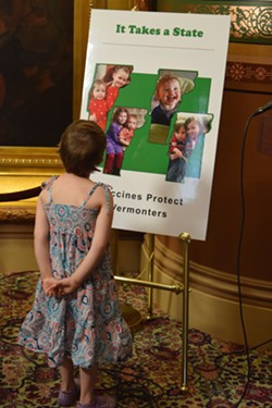 Mia Hockett's daughter, Merin, looks at a poster that a group of Vermont mothers, including hers, put together to emphasize the importance of immunizations. - TERRI HALLENBECK