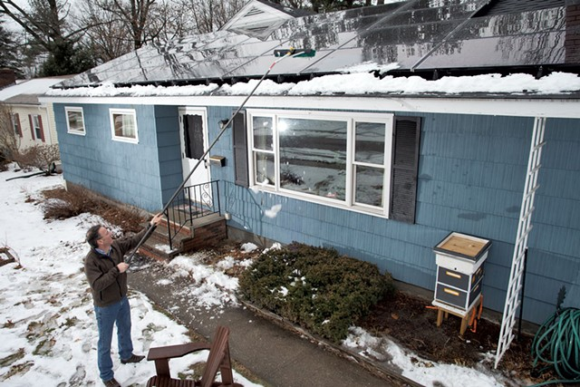 Nik Ponzio cleans the solar panels  on his retrofitted home - MATTHEW THORSEN