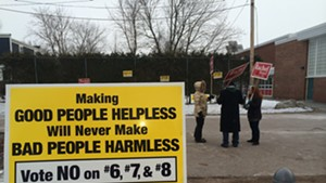One of many signs outside of Lawrence Barnes Elementary School  urging voters to reject three gun control measures on the ballot. In the background are Ward 3 City Councilors Rachel Seigel and Vince Brennan, both Progressives, and Burlington City Progressive Party Chair Kyle Sillman-Smith.