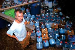 Paul Butler of Dog River Aternative Fuels stands with some of the used cooking oil his company will turn into biodiesel, a biodegradable fuel. - MARK BUSHNELL