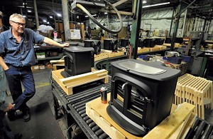 JEB WALLACE-BRODEUR - Rick Grant looks over an assembly line of woodstoves