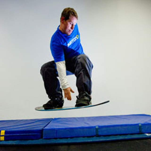 Scott Adam jumps on a trampoline designed to train snowboarders how to do tricks - ANDY DUBACK