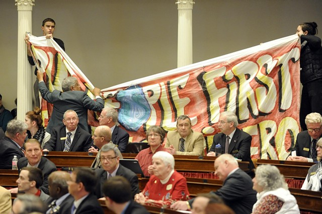 Sergeant-at-Arms Francis Brooks pulls down a banner held by single-payer protesters at Gov. Peter Shumlin's inauguration. - JEB WALLACE-BRODEUR