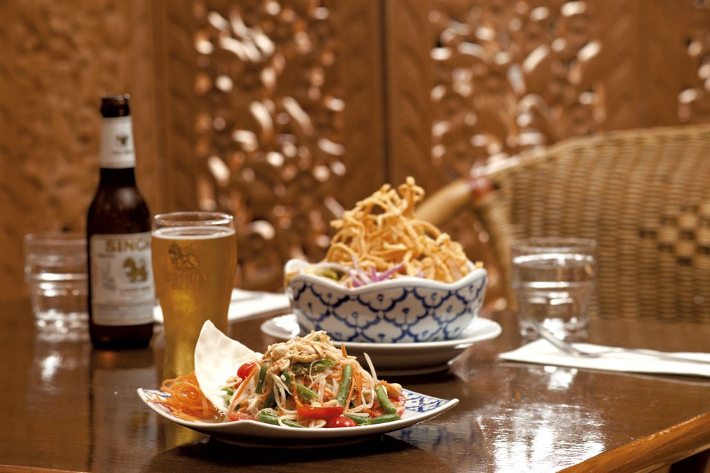 Som tum salad (foreground), kao soi - MATTHEW THORSEN