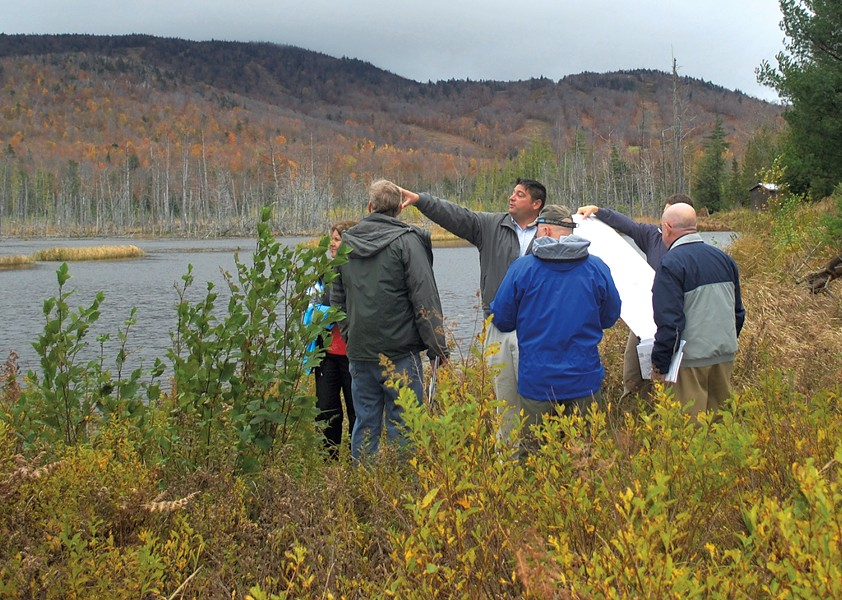 State officials and Adirondack Club and Resort representatives discussing the proposal alongside Cranberry Pond in 2011 - COURTESY OF JESSICA COLLIER OF THEADIRONDACK DAILY ENTERPRISE