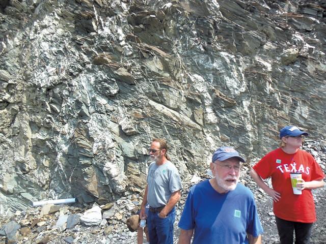 Tour participants gaze at a quarry face.