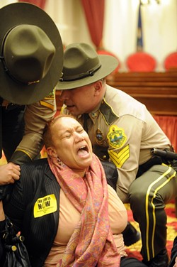 Vermont State Police remove Sheila Linton of Brattleboro from the chamber of the Vermont House. - JEB WALLACE-BRODEUR
