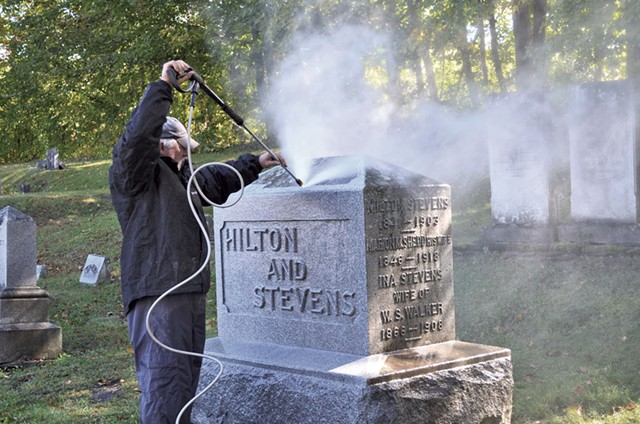 Jim Woodman cleaning mold and lichen off a headstone - ALICIA FREESE
