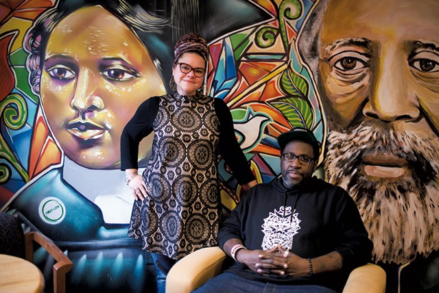 "Jennifer Herrera Condry and Will ""KASSO"" Condry in front of a mural depicting Mary Annette Anderson and Martin Henry Freeman - CALEB KENNA"