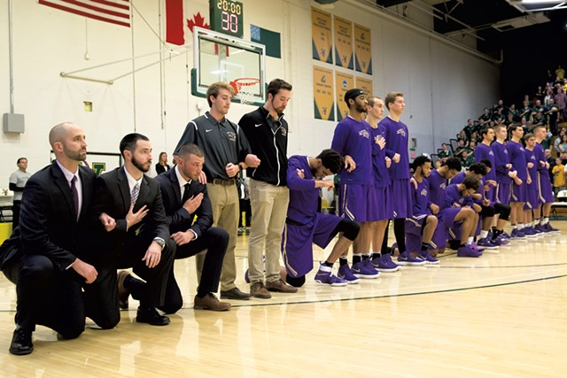 Saint Michael's College men's basketball players kneel during the anthem in an exhibition game at the University of Vermont - FILE: JAMES BUCK