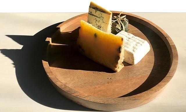 Piedmont and Lombardy cheese board at Dedalus Wine Shop: Robiola Tre Latti Fico (in leaf), Bergamino di Bufala (white square), Castelmagno d'Alpeggio (golden), Blu Imperiale (blue) - SUZANNE M. PODHAIZER
