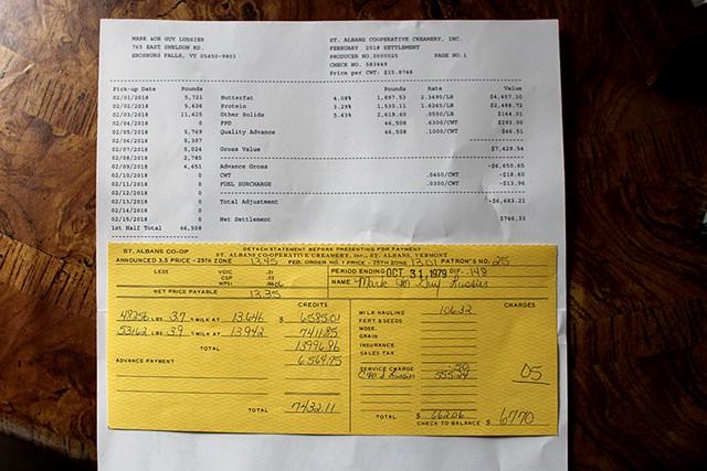 Mark Lussier's milk checks from February 2018 (top) and October 1979. Base price per hundred pounds of milk highlighted. - PAUL HEINTZ