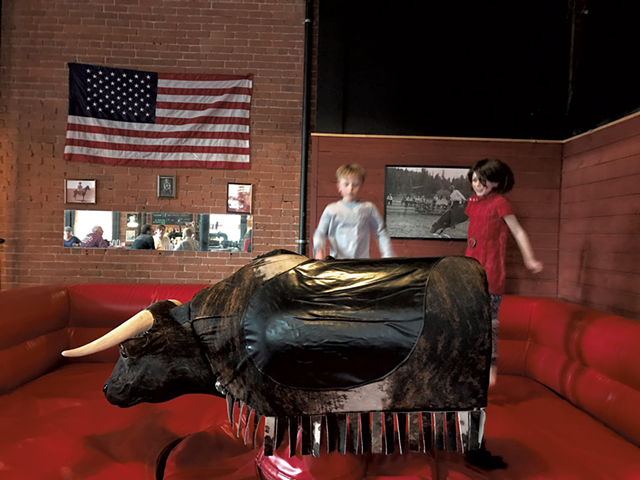 Reaney McKinley, 9, and Della Connor, 7, play in Rough Cuts mechanical bull ring - SALLY POLLAK