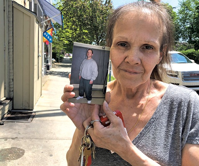 Nancy Davis holding up a photo of her incarcerated son, Jason Anderson - ALICIA FREESE