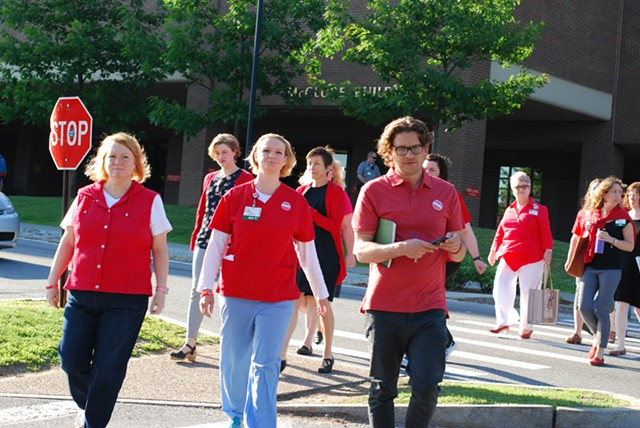Union leaders, including Julie MacMillan, center, cross the street to make their announcement. - SARA TABIN