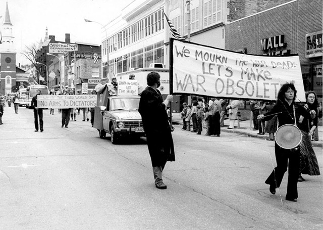 Robin Lloyd banging a drum on Burlington's Church Street with the Peace & Justice Center's Wendy Coe in the background, circa 1980 - COURTESY OF GREG GUMA