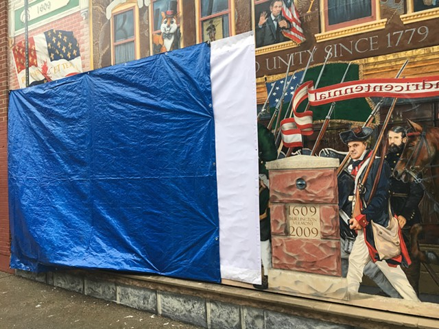 """A tarp covers the vandalized section of the """"Everyone Loves a Parade!"""" mural in Burlington. - MATTHEW ROY"""