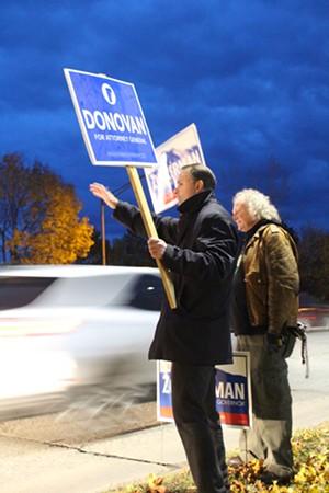 Attorney General T.J. Donovan waves to motorists Monday night in South Burlington. - PAUL HEINTZ