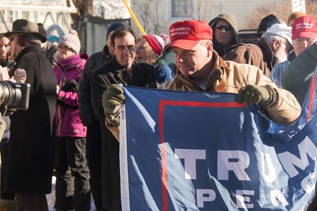 Gus Klein raising Trump campaign flag - DEREK BROUWER
