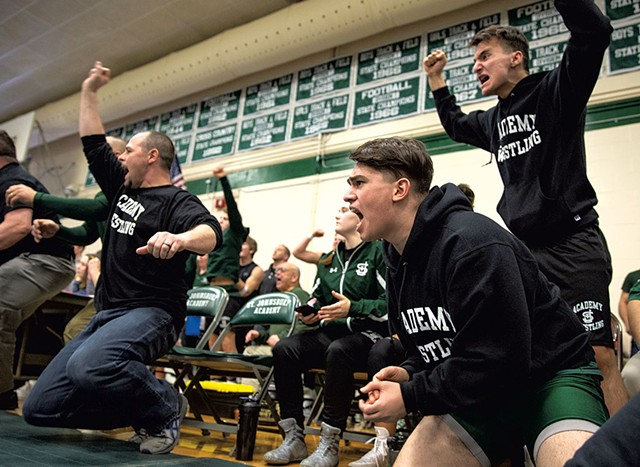 Ayman Alsalloumi (second from right) and Majd Alabas (right) cheering with their team during a meet - JAMES BUCK