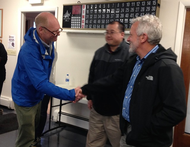 Winooski Superintendent of Schools Sean McMannon (left) shakes hands with school board chair Mike Decarreau (right) as school board member Alex Yin looks on. - MOLLY WALSH