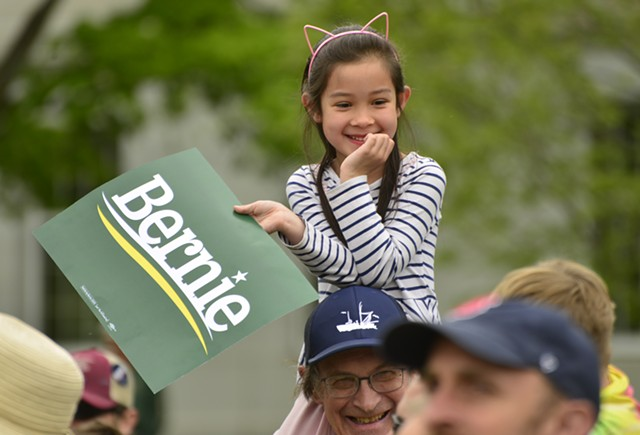 Mai Huynh Parke, 6, of Montpelier takes in the crowd from atop the shoulders of her dad, Ethan, 68, during a Bernie Sanders rally Saturday in Montpelier. - STEFAN HARD