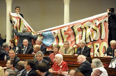 Protesters, led by the Vermont Workers' Center, hang a banner at Gov. Peter Shumlin's inauguration in January. - FILE: JEB WALLACE BRODEUR