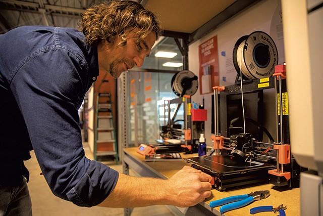 Travis Vogel working with a 3D printer - JAMES BUCK