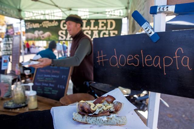 George van Vlaanderen serving a grilled sausage sandwich at the Doe's Leap Farm booth - JAMES BUCK