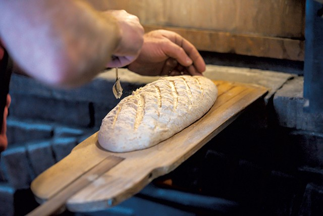 Scoring a sourdough bâtard before putting it in the oven - GLENN RUSSELL