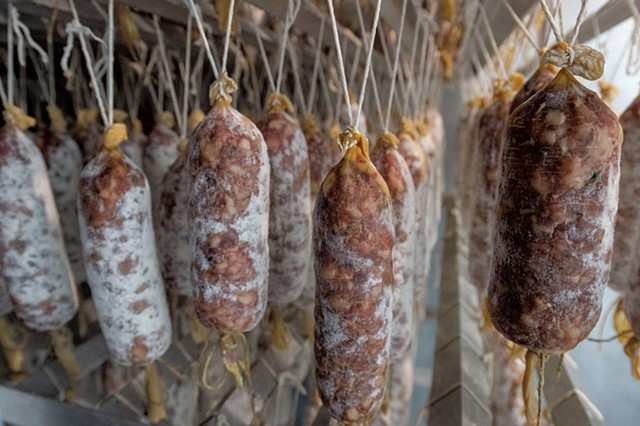 Racks of aging Babette's Table salamis - JEB WALLACE-BRODEUR