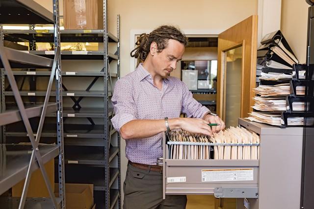 Chief herbalist Guido Masé combing through paperwork - OLIVER PARINI