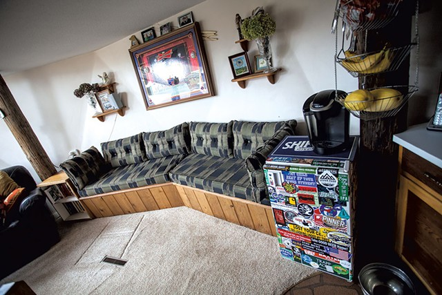 A beer fridge flanks a - built-in couch. - TOM MCNEILL