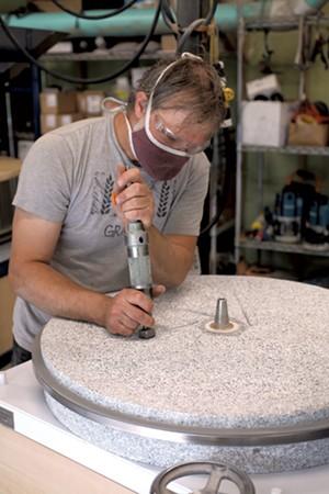Andrew Heyn sharpening a mill stone - JESSICA OJALA ©️ SEVEN DAYS