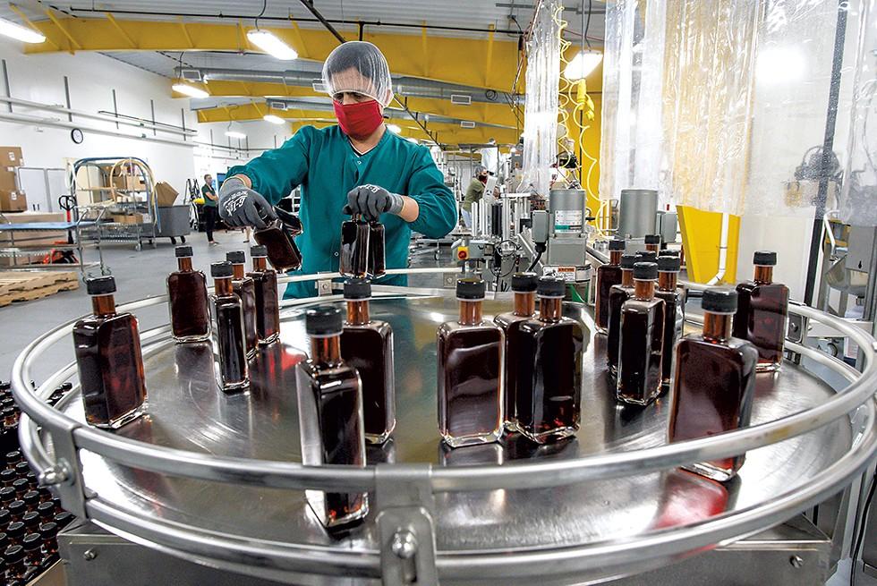 Krishna Upadhyay checking bottles of maple syrup - GLENN RUSSELL ©️ SEVEN DAYS