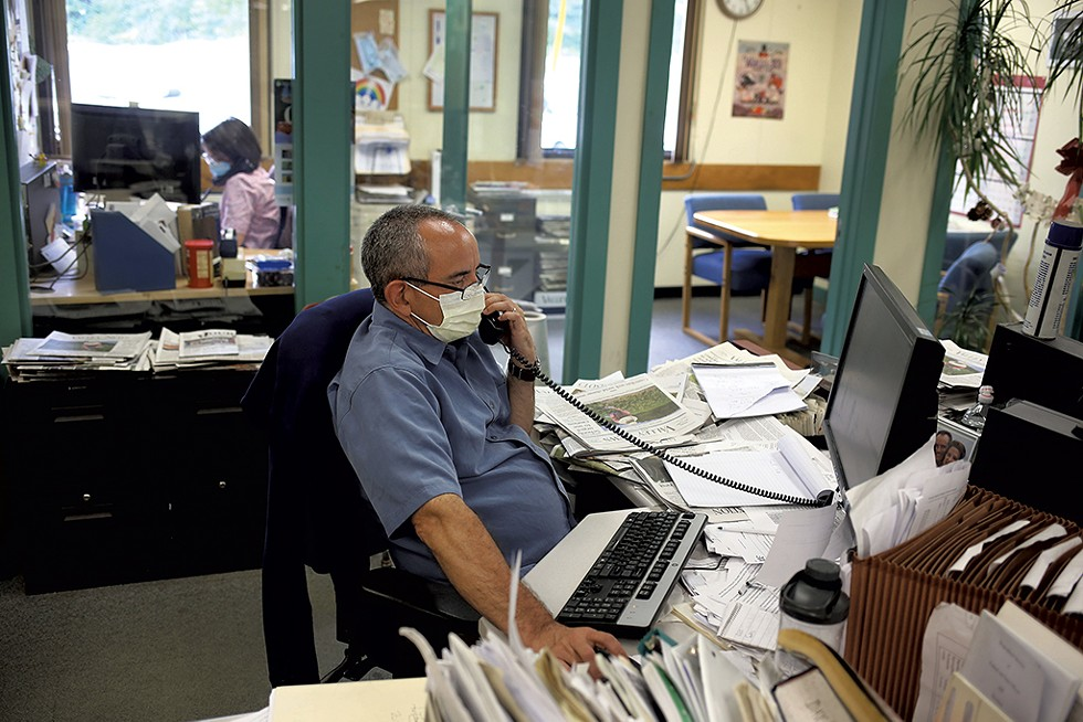 Editors John Gregg and Maggie Cassidy (in background) attending the daily news meeting by phone - SARAH PRIESTAP ©️ SEVEN DAYS